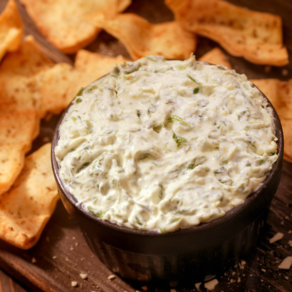 Bowl of artichoke dip surrounded by pita chips