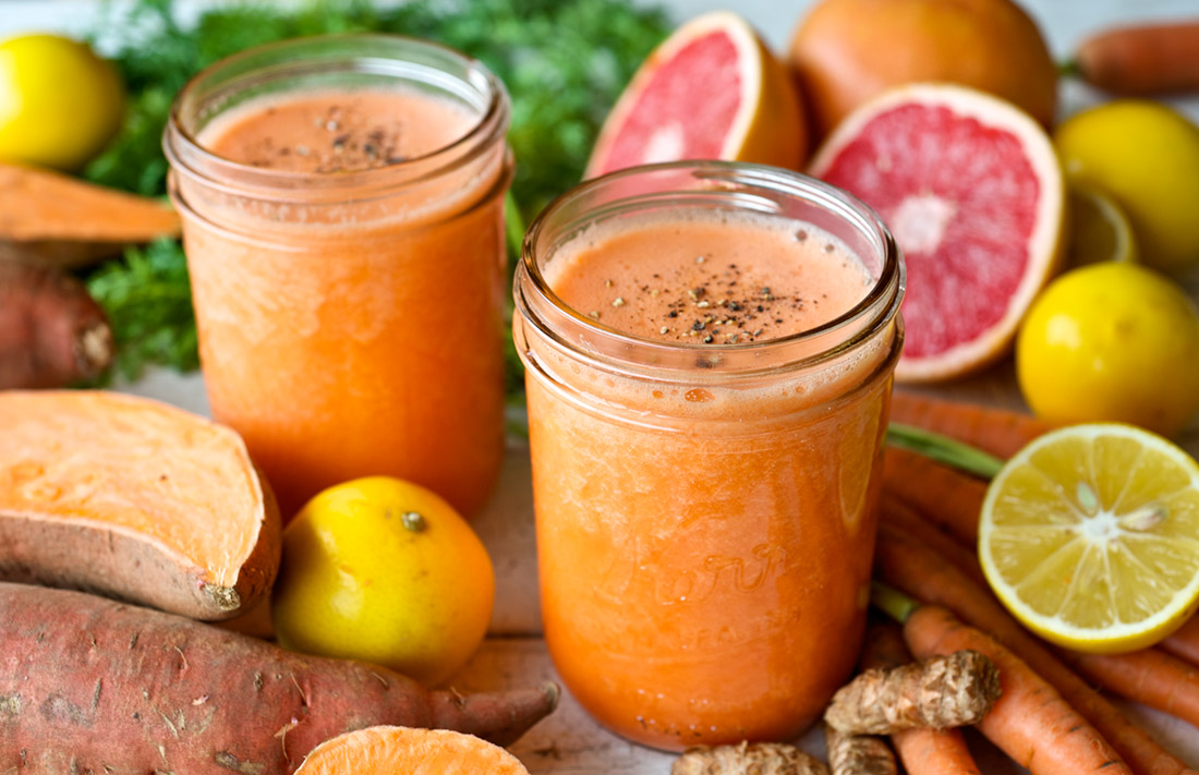two mason jars of fresh pressed juice orange in color on a table surrounded by fresh produce