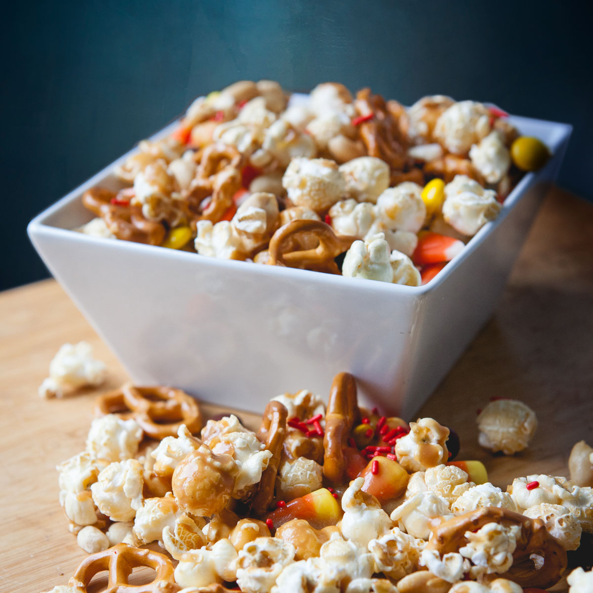 Popcorn and pretzel Halloween mix in a white bowl