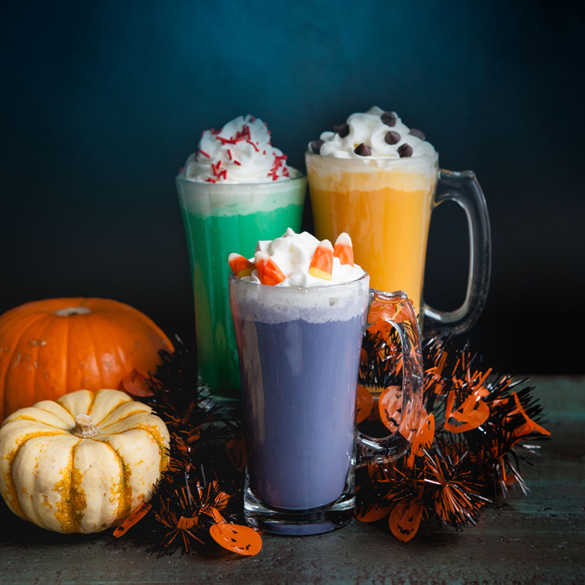 Three colorful drinks with Halloween candy and whipped cream on top surrounded by spooky decorations