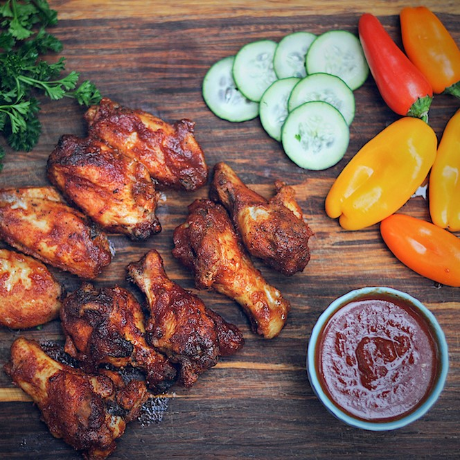 baked chicken wings next to container of sauce, cucumbers, and peppers