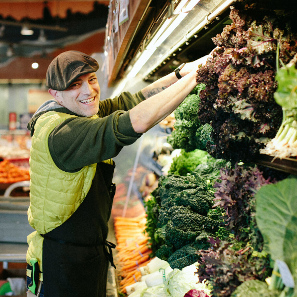 New Leaf Community Markets employee stocking the produce section with local organic options