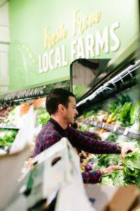New Leaf Community Markets employee stocking fresh, local and organic produce