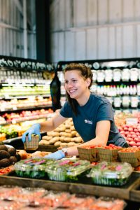 New Leaf Community Markets employee stocking produce in our newest location in Aptos, California.