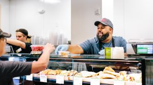 New Leaf Community Markets deli employee handing prepared foods to a customer