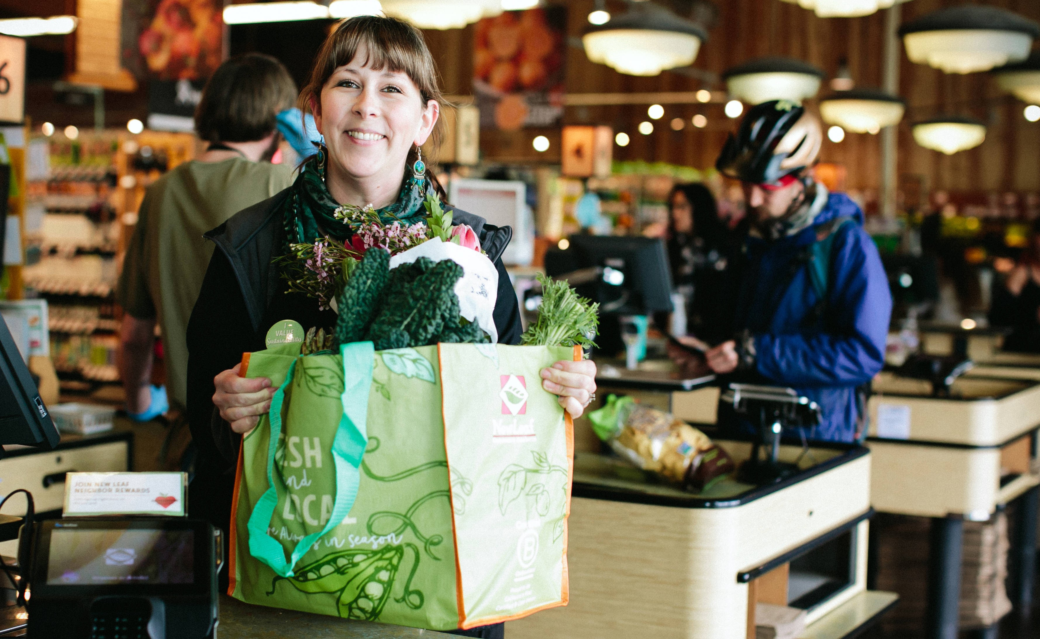 New Leaf Community Markets grocery store cashier smiling and while handing over a reusable bag full of groceries